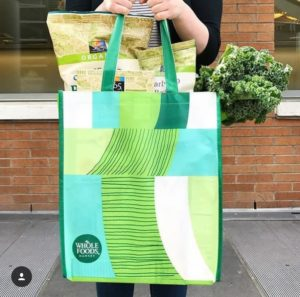 Person walking with a Whole Foods Market shopping bag