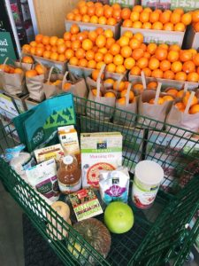 Whole Foods Market shopping cart with groceries in front of a display of oranges