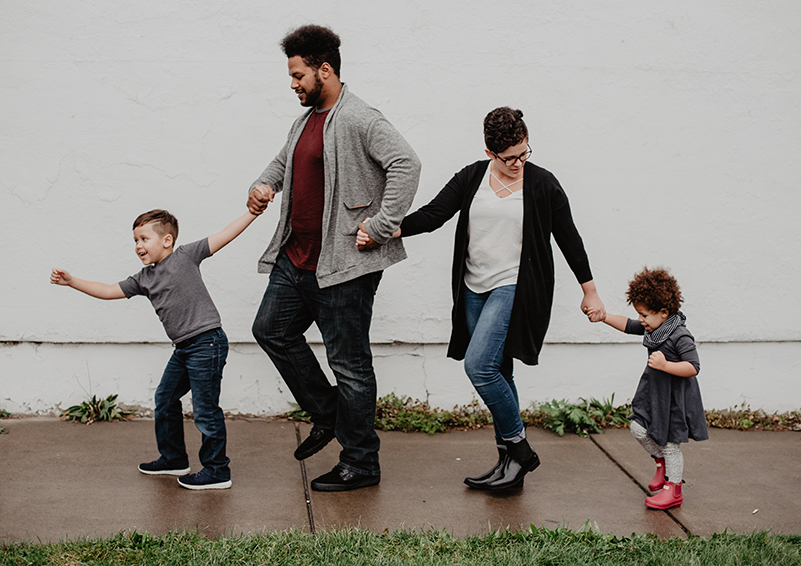 A multi-racial family of 4 holds hands & walks down a wet sidewalk in rainboots