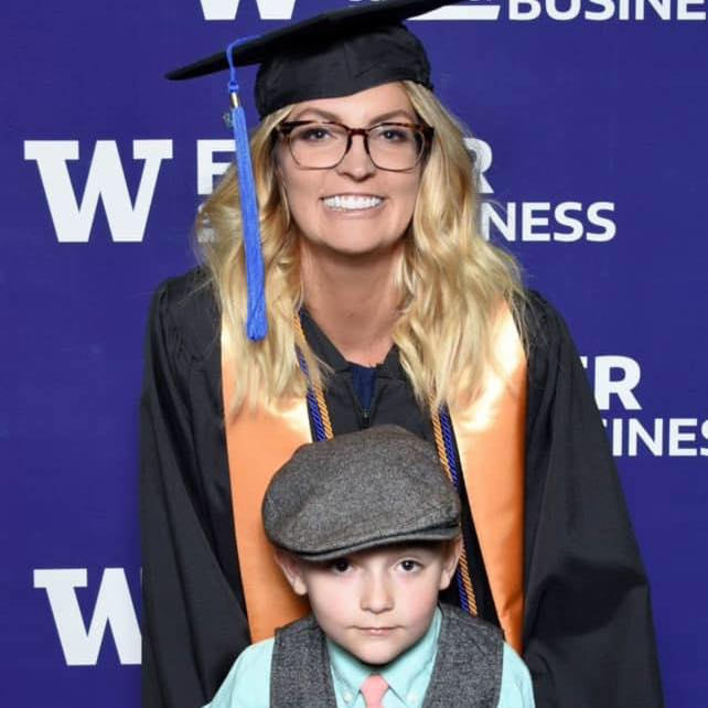 A blonde woman with glasses with her young son at her University of WA graduation