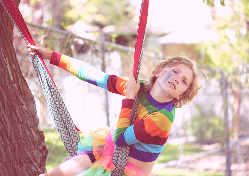 Child in rainbow clothing swinging from a hammock