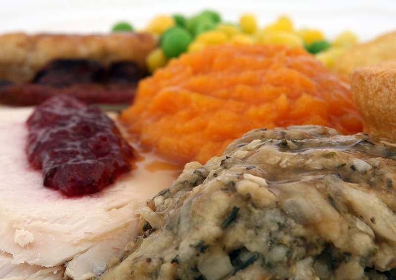 Thanksgiving foods: turkey with cranberry dressing, stuffing, squash, corn, & peas