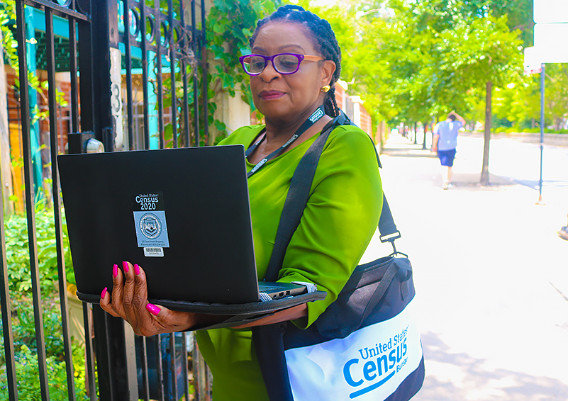African-American woman with purple glasses and a green top with a 2020 US Census bag and laptop