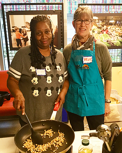 (L to r): Alma Britton and Peggy Keene toast walnuts for pesto in a Cooking Matters class.