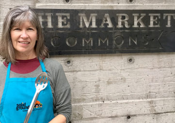 Cooking Matters volunteer Peggy Keene, wearing a teal Solid Ground apron and holding a slotted spoon
