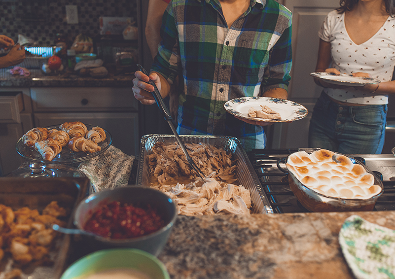 People filling plates at a holiday meal buffet
