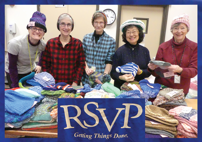 Five women wearing knitted hats, standing in front of a table full of knitted items, with a blue RSVP tablecloth logo in front of it.