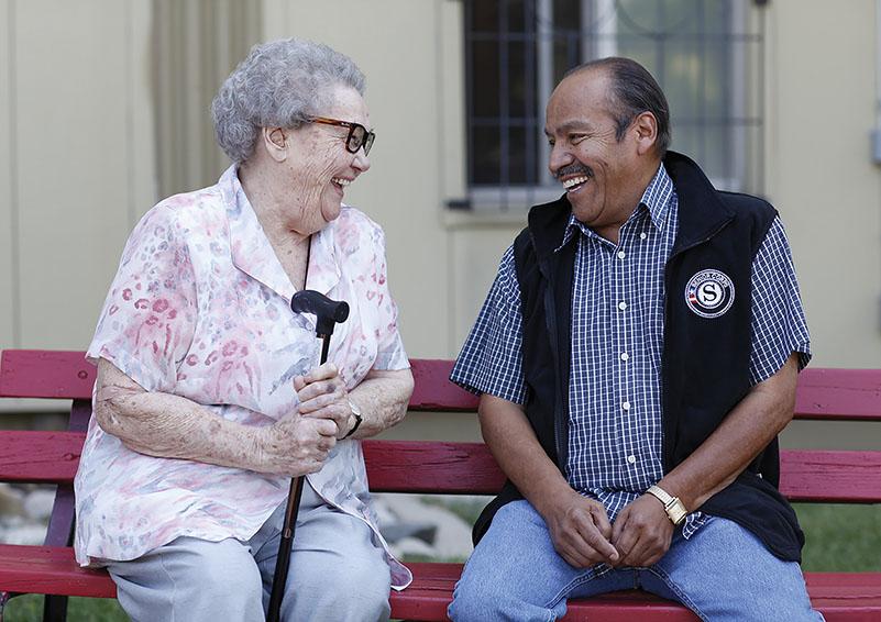 Elderly lady with cane sitting next to Senior Volunteer on bench.