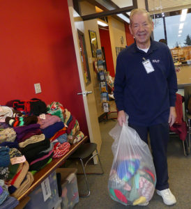 Man with a bag of warm knitted items for donation, Nov. 2012