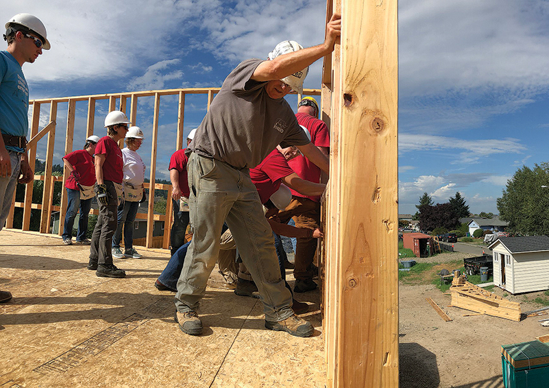 Habitat for Humanity volunteers in hard hats put up wood frame for a 2-story house