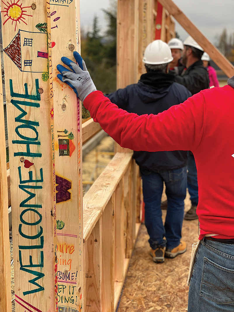 "Habitat for Humanity volunteers wrote a ""Welcome Home"" message on a framing beam."