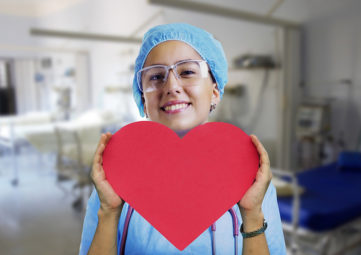A nurse in blue scrubs holds a red paper heart in her hands