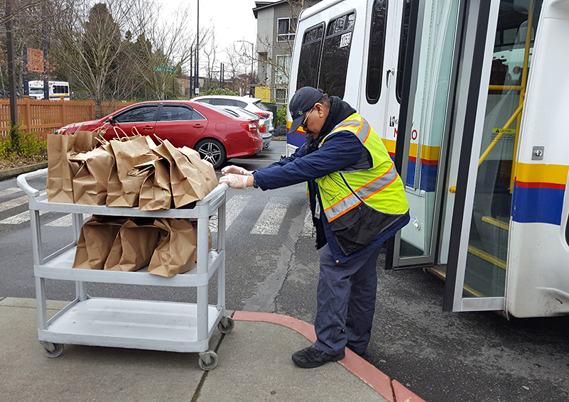 Access bus driver pushing cart with brown bags containing food