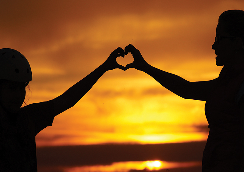 Silhouette of a mother & daughter holding their hands up to form a heart in front of a brilliant orange sunset