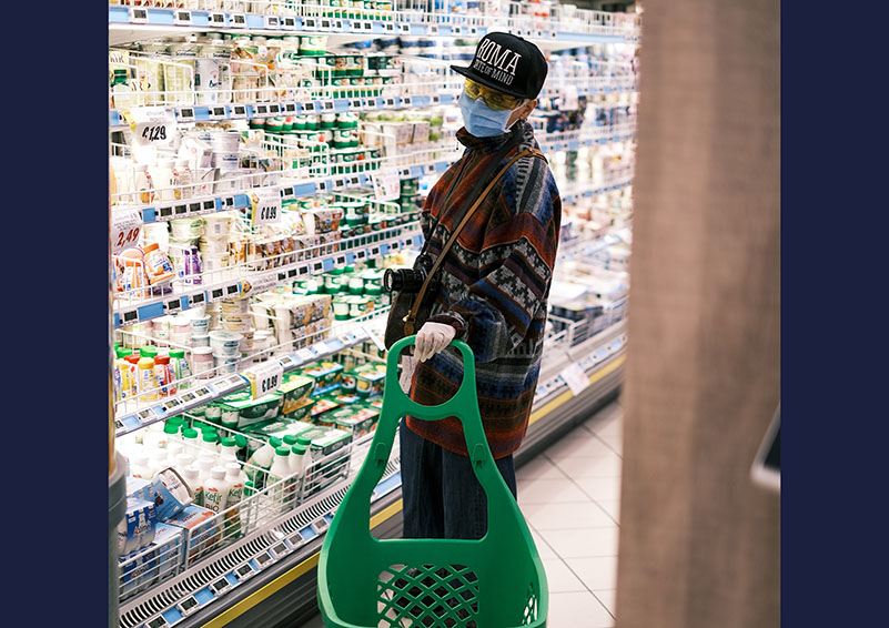 Asian woman in mask, cap & gloves shops at a grocery store