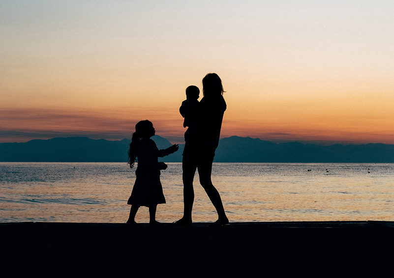 Woman with children on the beach