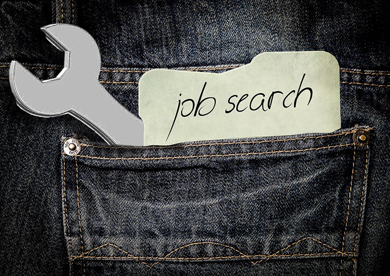 "Graphic of the back pocket of charcoal gray jeans with gold stitching. A wrench and a slip of paper with ""job search"" on it is sticking out of the pocket."