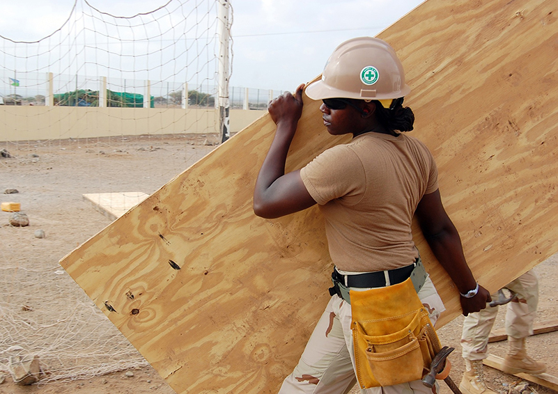 Black woman construction worker in hard hat and sunglasses wearing khaki clothes carries a large piece of plywood across a sandy lot