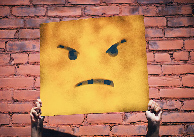 Person holding a yellow square sign with an angry face painted on.