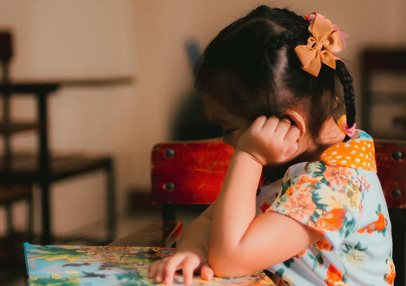 Profile of a small Asian girl with a bow and braid sitting at a desk reading a picture book