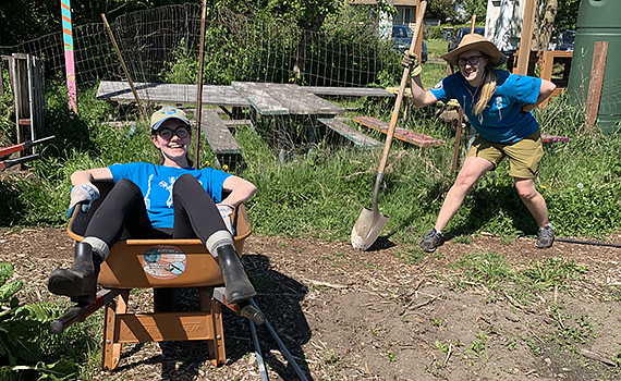 One woman lounges in a wheelbarrow while another poses with a shovel at an urban farm