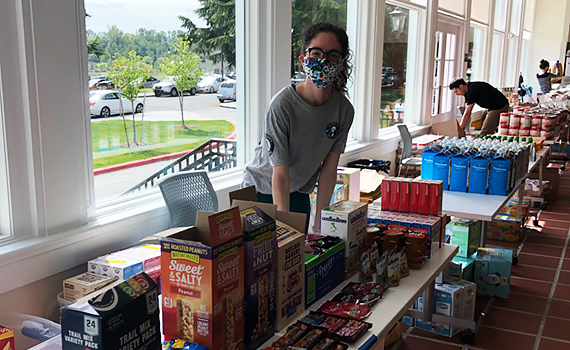 A woman wearing a mask & glasses with black hair pulled back stands behind a table stacked with food pantry items