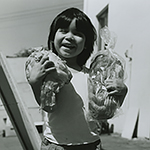 Black and white photo of a small boy grinning, holding a large head of lettuce in one arm and a loaf of bread in the other