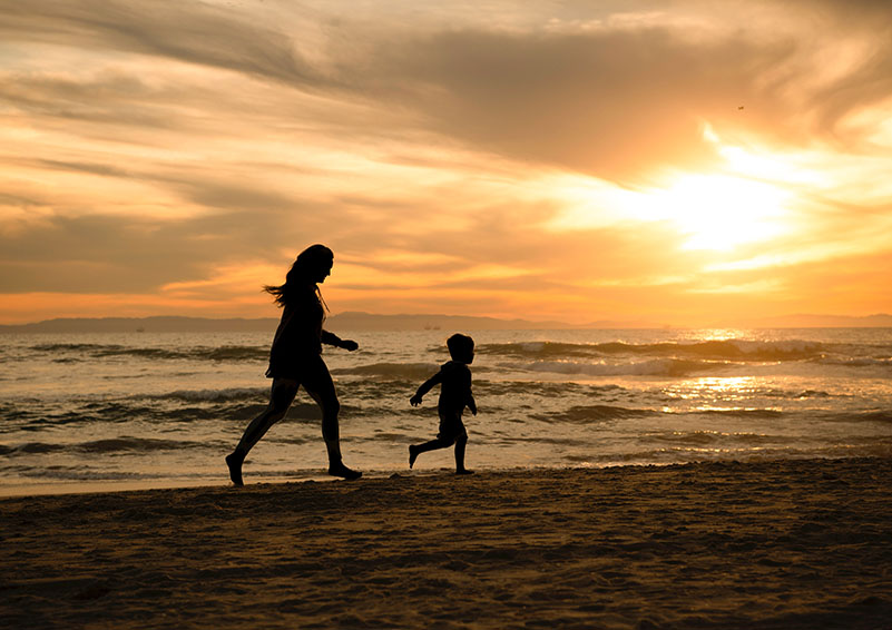 Silhouetted image of mother and child running on the beach during a sunset.