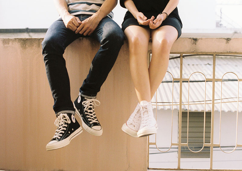 Two teens sitting on a wall.