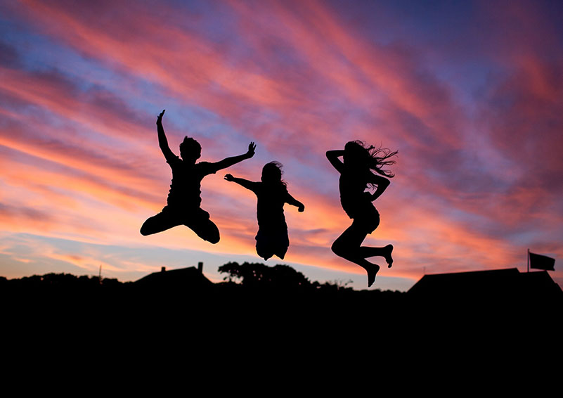 Silhouette image of three kids jumping for joy in front of sunset.