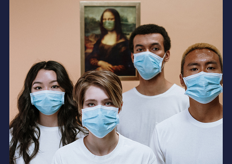 Four young adults, one Asian, one white, two black, wearing white T-shirts & blue face masks, with a picture of the Mona Lisa wearing a face mask behind them