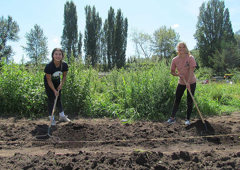 Two teen girls, one with a rock rake and one with a shovel, pose grinning while prepping a garden bed for planting.