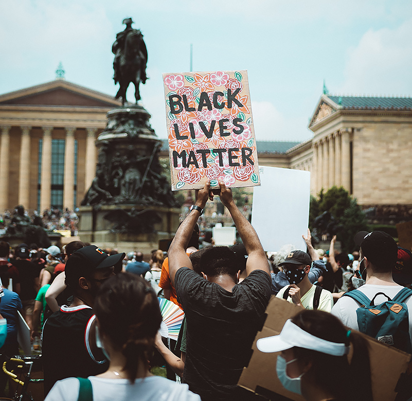 Black man bows his head while holding up a BLACK LIVES MATTER sign (black lettering on an ornate floral background) amidst a crowd, standing in front of a Confederate statue