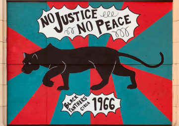 "Mural of a black panther (animal) on a blue & red striped background, with ""No Justice, No Peace"" in a thought bubble above it, and ""Black Panthers circa 1966"" below it"
