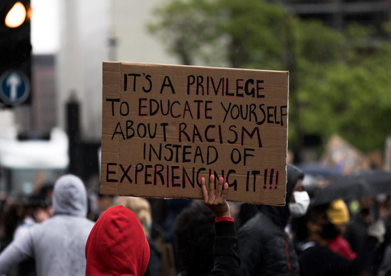 Group of protesters viewed from the back, one holding a sign that reads 'It's a privilege to educate yourself about racism instead of experiencing it!!!'