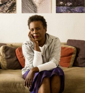 Picture of a Black woman sitting on a couch with her face resting on her right hand, posing for the camera.
