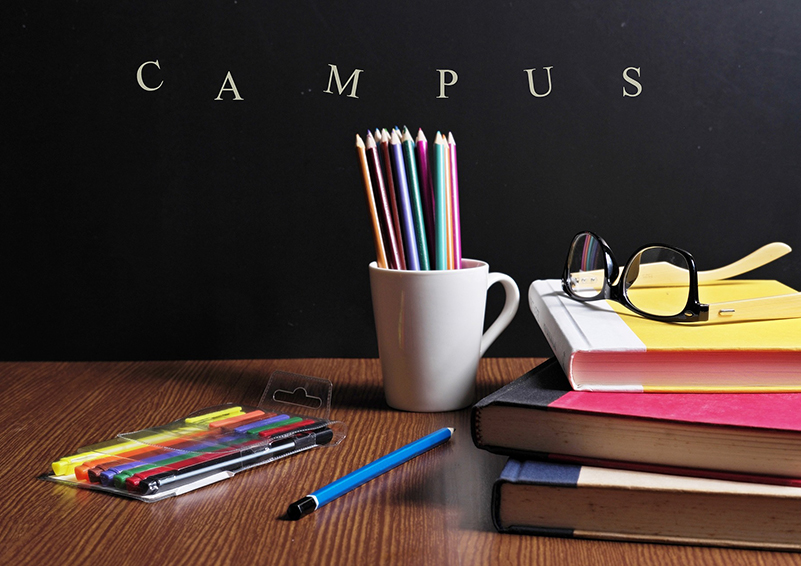 Brown table with colored pencils lying on it and in a white mug. Stack of 3 hard-bound books with eyeglasses on them. Blackboard in the background with the word CAMPUS on it.