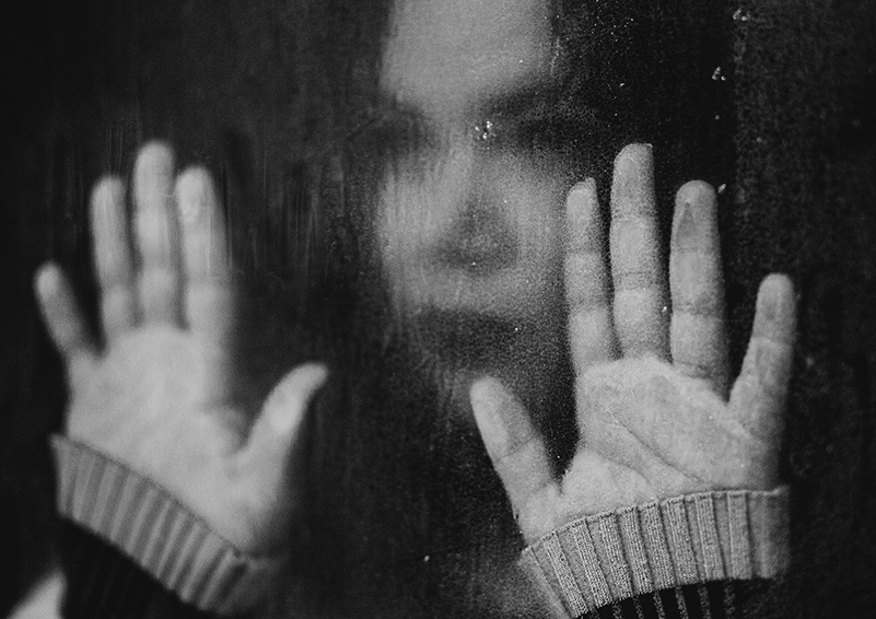 Black & white photo of a woman staring mournfully out of a rain-streaked window with her hands pressed against the glass.