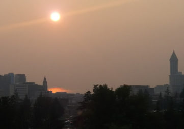 Seattle skyline through an orange-grey haze of wildfire smoke, with an orange sun above
