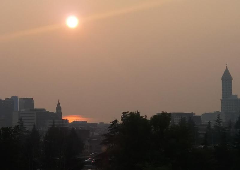 Seattle skyline through an orange-grey haze of wildfire smoke, with an orange sun above