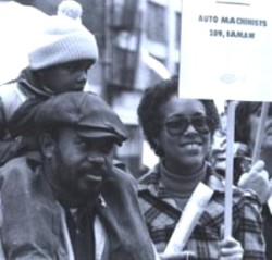 Black and white photo of man in cap with his son on his back, and his wife holding an auto machinists protest sign
