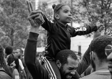 Grayscale photo of a young girl sitting on a man's shoulders with both their hands in the air at an outdoor group gathering