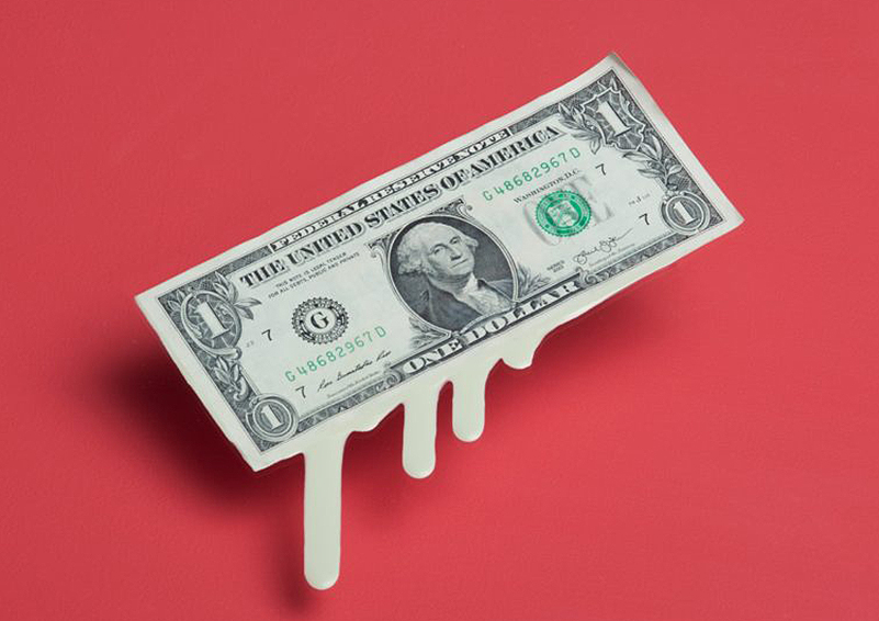 Melting, dripping dollar bill on a red background.