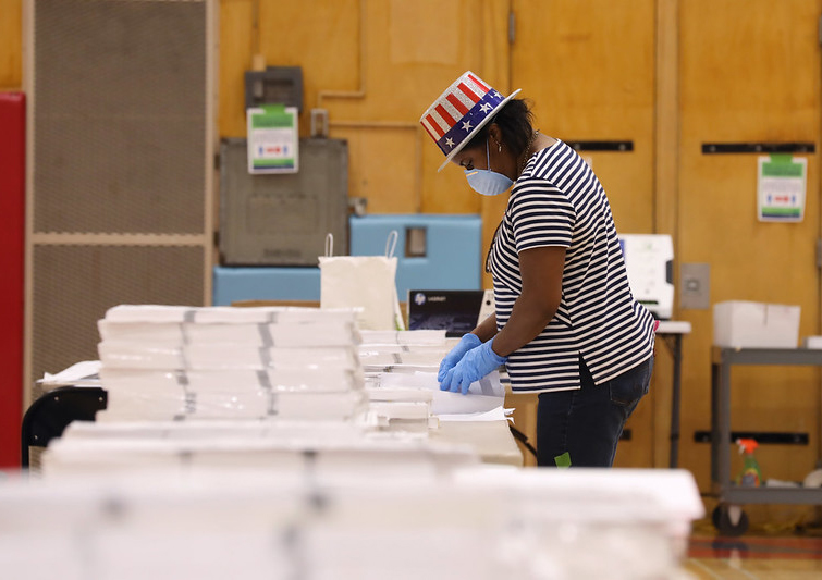 "poll worker in ""Uncle Sam"" flag hat prepares paper ballots"