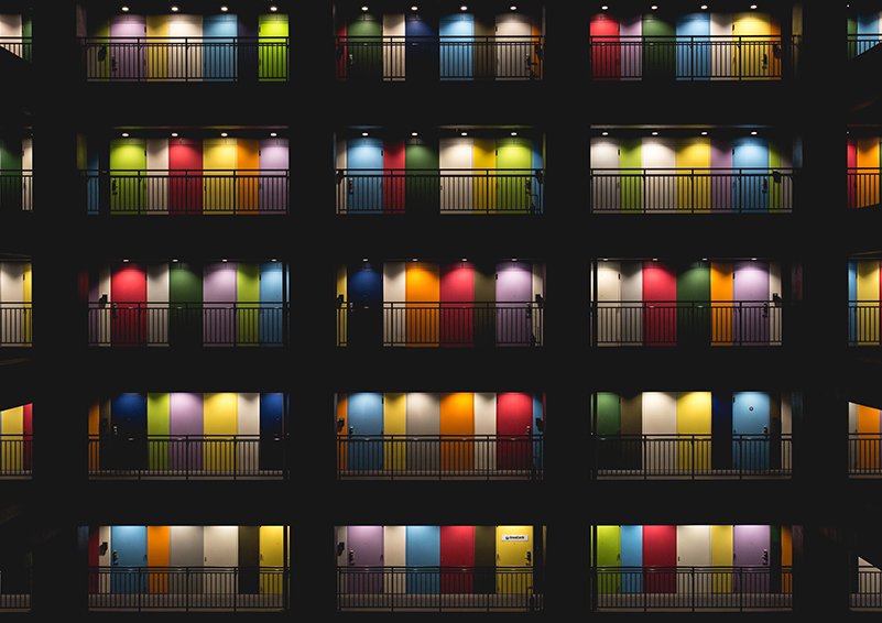 Five stories of an apartment building with brightly lit, multi-colored doors