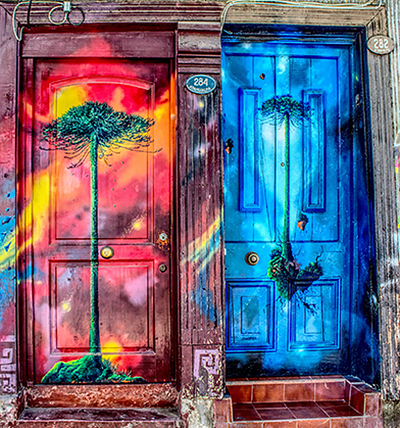 Two brightly painted doors side by side, one pink, red, and yellow with a green tree on it, and one blue