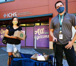 Two ICHS healthcare workers holding the donated Starbucks coffee