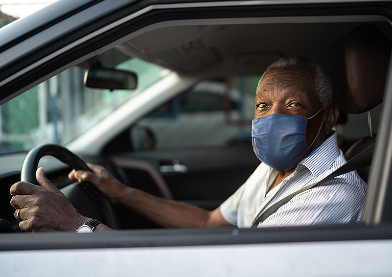 immigrant man wearing a blue mask sits in his car