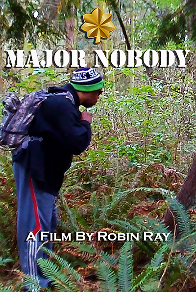 Movie title page for MAJOR NOBODY, A FILM BY ROBIN RAY. Robin is in the woodswearing a Seahawks cap, navy hoodie, dark sunglasses, and a purple backpack.