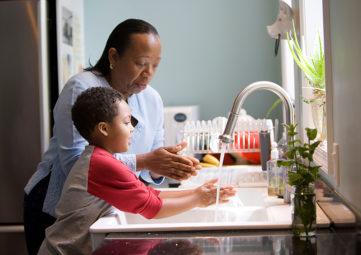 Mother & son wash hands at kitchen sink, plants in windowsill